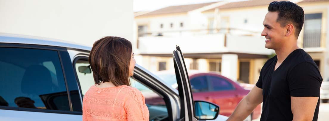 Mujer a punto de subir al coche y un hombre invitándole a entrar sujetando la puerta