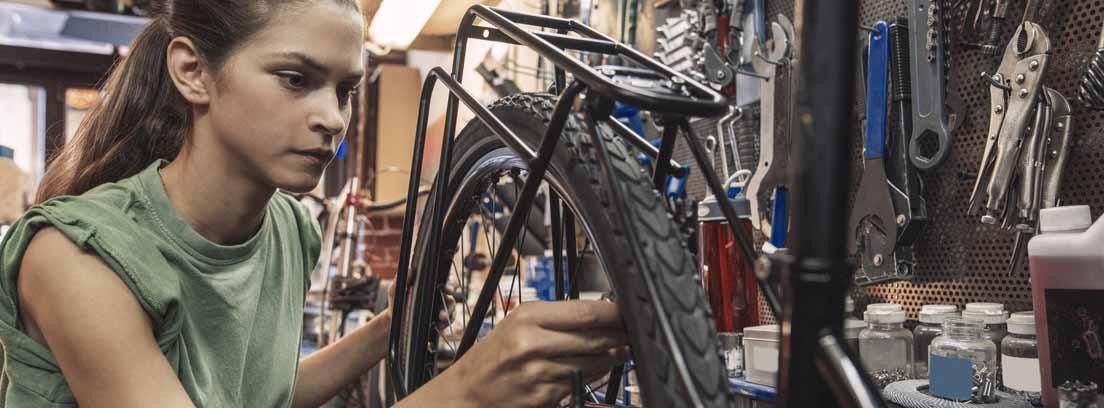 Mujer reparando la rueda de una bicicleta