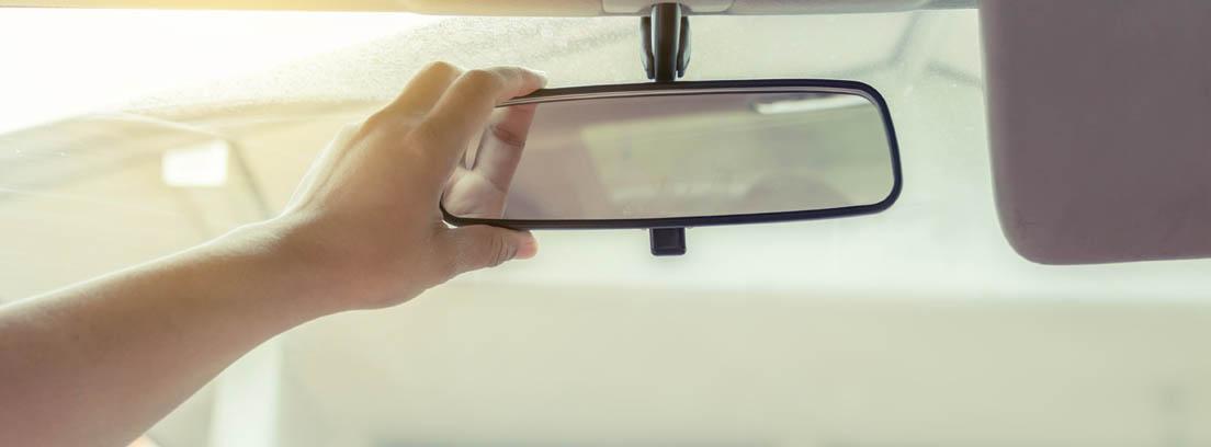 Conductor ajustando el espejo retrovisor interior