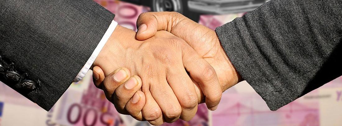 Dos manos estrechándose sobre del dibujo de coche descapotable y billetes de euro