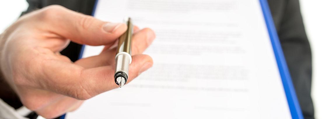 Mano sostiene un bolígrafo hacia delante y unas hojas escritas con fondo blanco.
