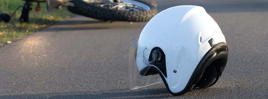Casco de moto en el suelo y motocicleta tirada en el suelo en segundo plano
