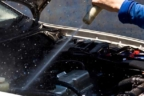 Una persona limpia con una pistola a presión el motor de un coche