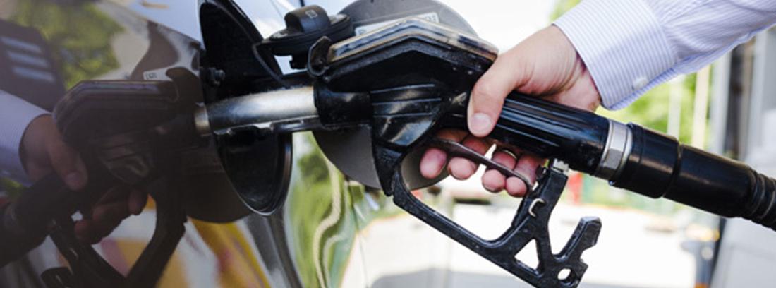 Una mano sostiene una manguera en el depósito de un coche