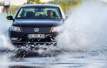 Vehículo circulando sobre una carretera con agua