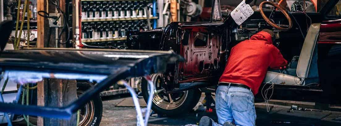 Persona arrodillada dentro de coche con piezas y herramientas alrededor