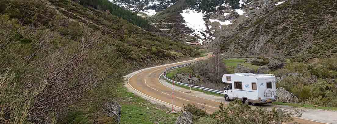 Caravana blanca por carretera entre montes y con fondo de montaña nevada