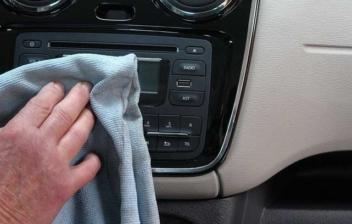 Mano sujeta bayeta azul sobre salpicadero frontal del interior de coche