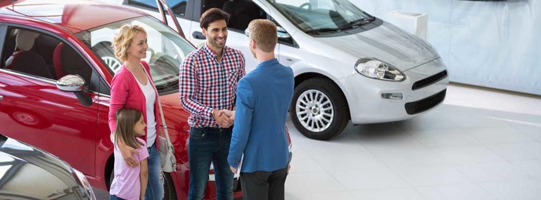 Dos hombres se estrechan la mano junto a varios coches una mujer y una niña