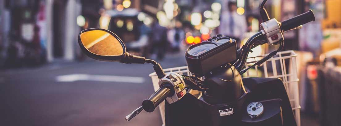 Primer plano del manillas de una moto con las luces de una ciudad al fondo