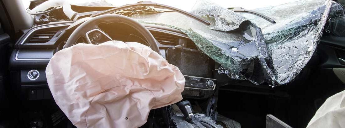 Interior de un coche con la luna rota y el airbag deshinchado tras una colisión