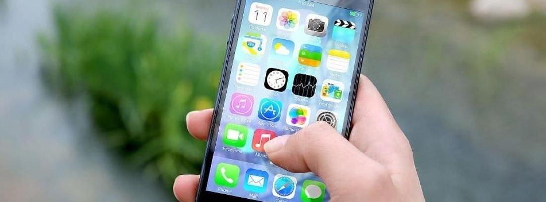 Mano sujeta un móvil con el dedo en la pantalla sobre icono de aplicación.