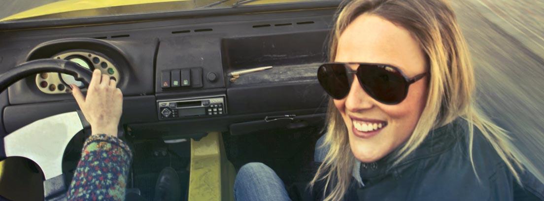 Mujer con gafas de sol dentro de coche y junto a conductor
