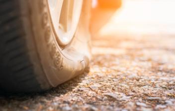primer plano de una rueda de coche pinchada