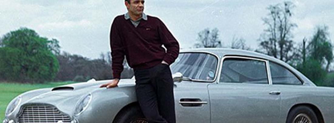 Sean Connery apoyado sobre un Aston Martin DB5