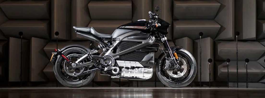 Moto negra y con detalles plateados sobre suelo y fondo negro.