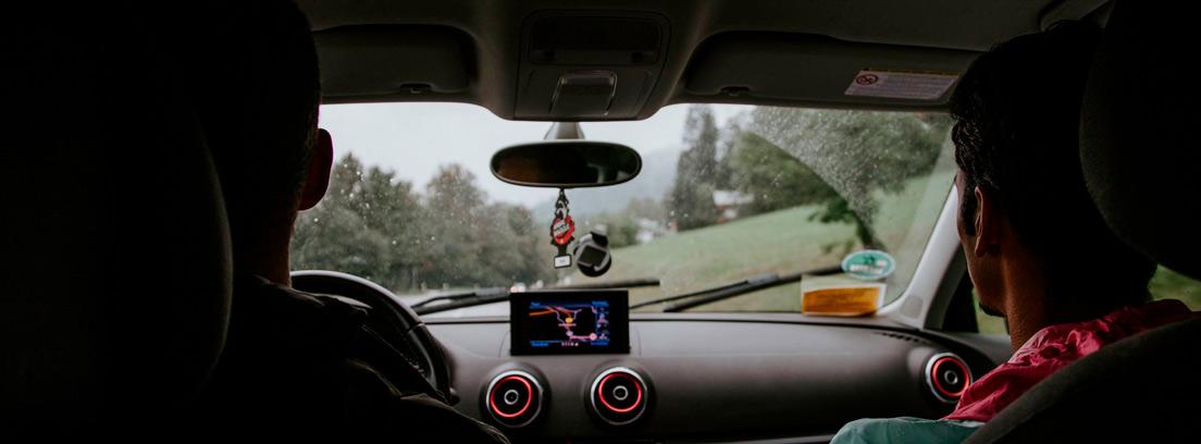 Vista interior de coche con dos personas dentro y gps con pantalla y cámara en el cristal