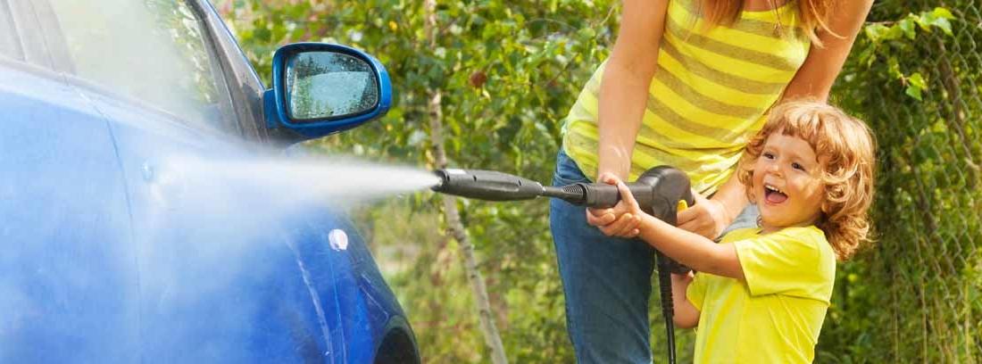 Niño con una manguera de agua a presión lavando el coche junto a una mujer