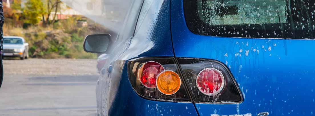 Vista de la parte trasera de un automóvil azul y una manguera de lavado a presión para el coche