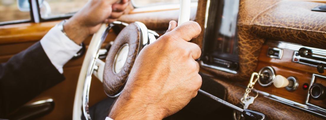 Manos sobre el volante de un coche antiguo, su mala colocación es uno de los errores en Seguridad Vial