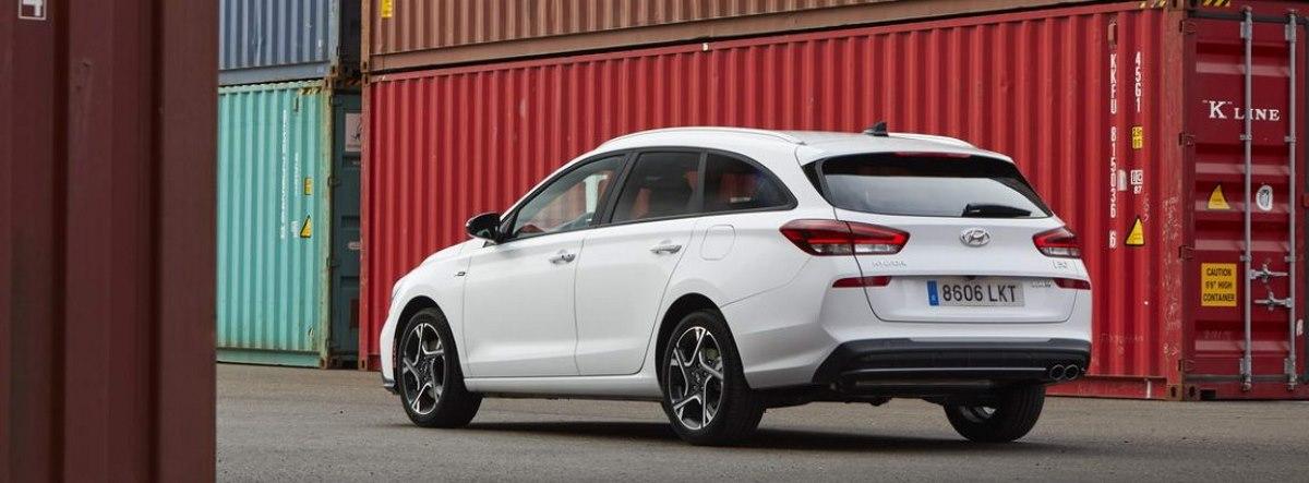 Hyundai I30 en color blanco circulando entre contenedores industriales