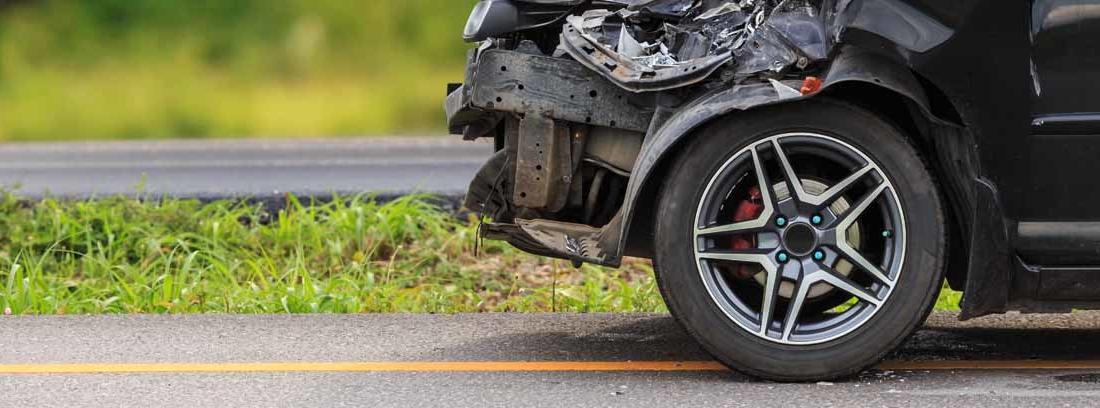 Vista parcial de la parte delantera de un coche completamente abollada por un accidente de Seguridad Vial