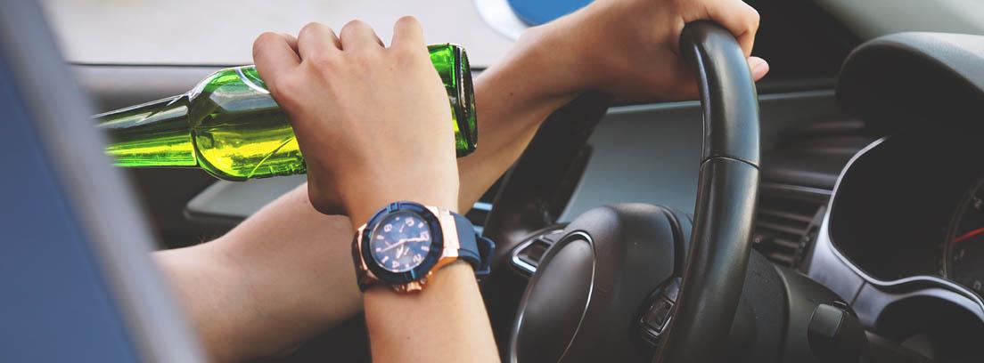 Vista parcial de un hombre bebiendo un botellín de cerveza dentro de un coche con una mano en el volante