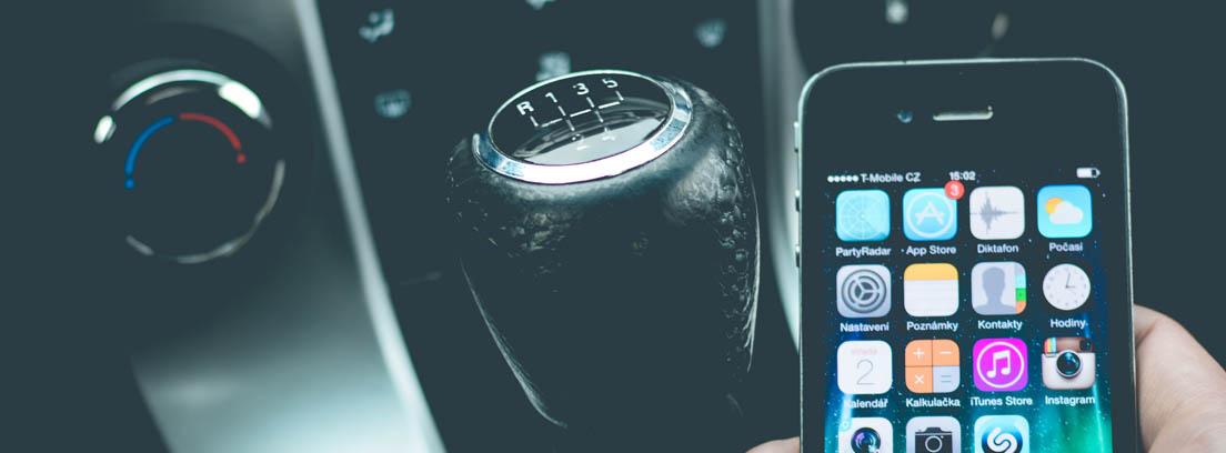 mano sujetando un teléfono móvil al lado de la palanca de cambios de un coche