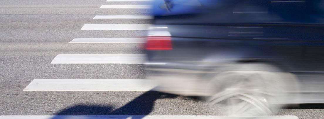 Imagen borrosa de un coche pasando por encima de un paso de peatones