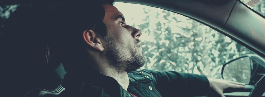 Hombre dentro de un coche con gesto cansado, un brazo sobre la puerta y la cabeza apoyada en el respaldo