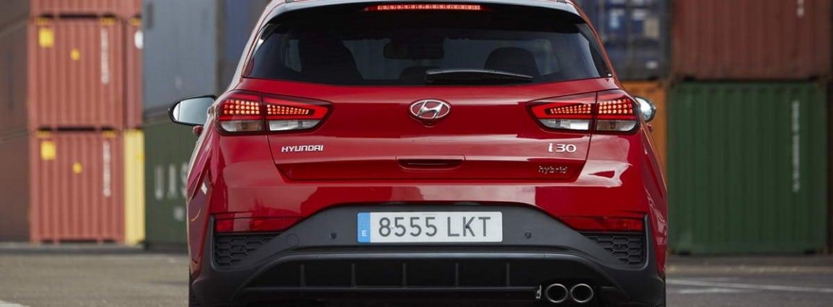 Vista trasera del Hyundai I30 en color rojo entre contenedores industriales