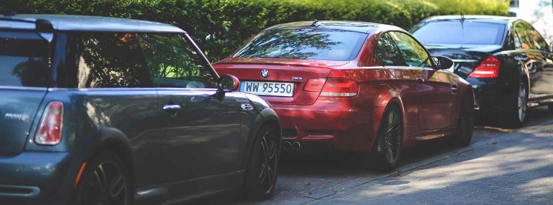 Coches de diferentes colores y tamaños aparcados en la calle.