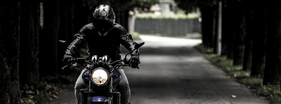motorista vestido de negro circulando por una carretera