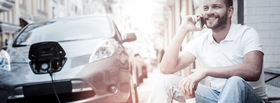 Hombre sonriente hablando por el móvil y al fondo un coche híbrido enchufable cargándose