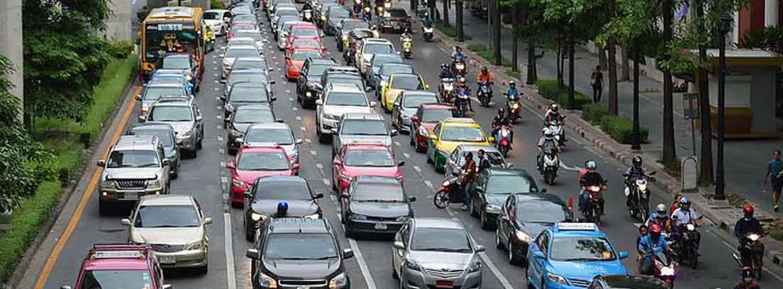 Diferentes hileras de coches y motos circulando por ciudad