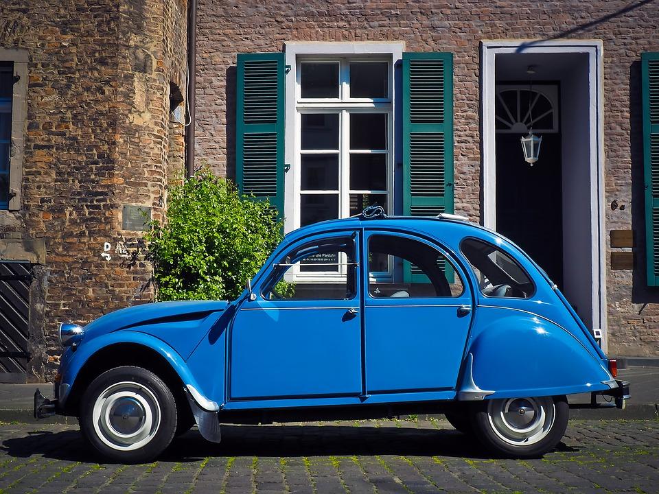Citroën 2CV en azul aparcado en la puerta de una casa
