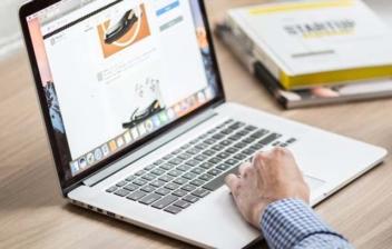 Persona consultando delante de ordenador portátil.