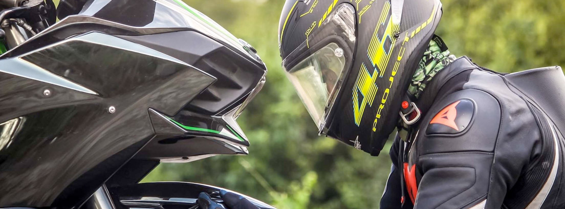 Piloto con casco integral frente a su moto