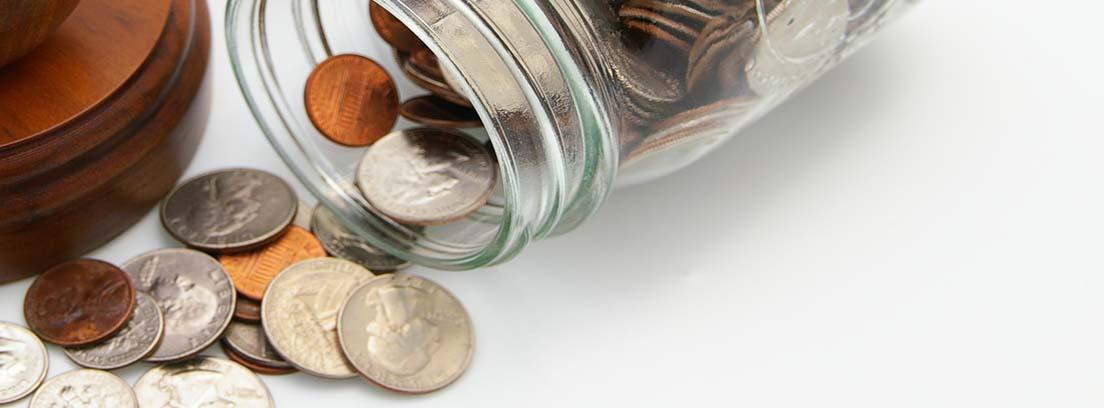 Mazo de madera junto a bote con monedas