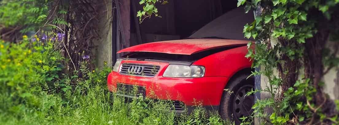 coche rojo estropeado abandonado en un cobertizo