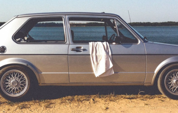 camiseta colgada de la ventanilla de un coche en la playa