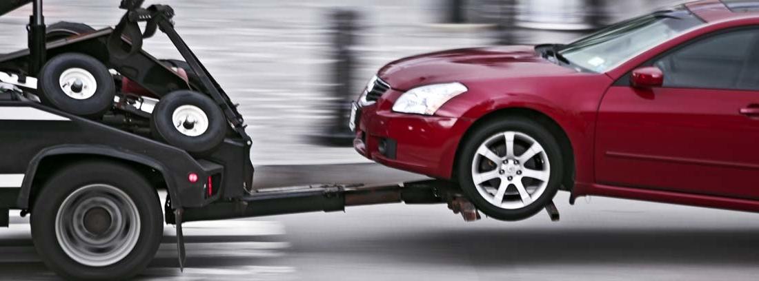 Vehículo rojo remolcadp por una grua