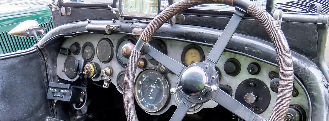 guantes de conducir colgados del volante de un coche antiguo
