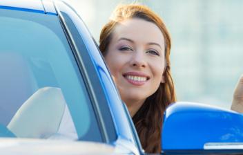 Mujer sonriente asomándose por la ventanilla de un coche con las llaves en la mano