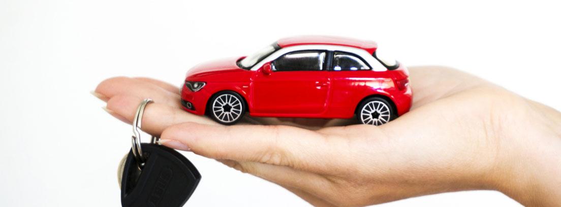 Coche de juguete y llaves de coche sobre la palma de una mano, como metáfora del mejor mes para comprar coche