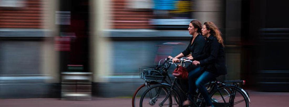 Dos mujeres en bicicleta por una calle urbana