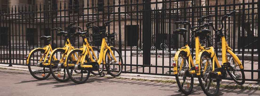 Varias bicis amarillas en una verja en ciudad