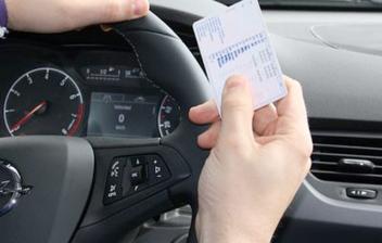 Persona al volante y con carné de conducir en la mano