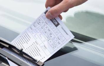 Mano colocando un papel con una notificación de una multa en el parabrisas de un