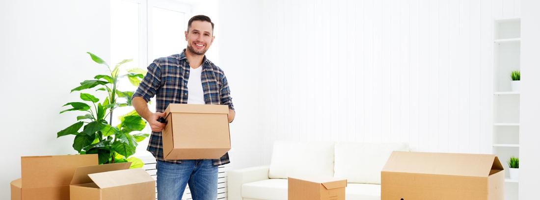 Hombre con caja de cartón en las mano y otros a su alrededor